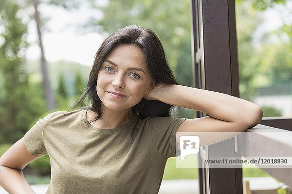 Porträt einer lächelnden Frau  die sich auf das Geländer des Hofes stützt.