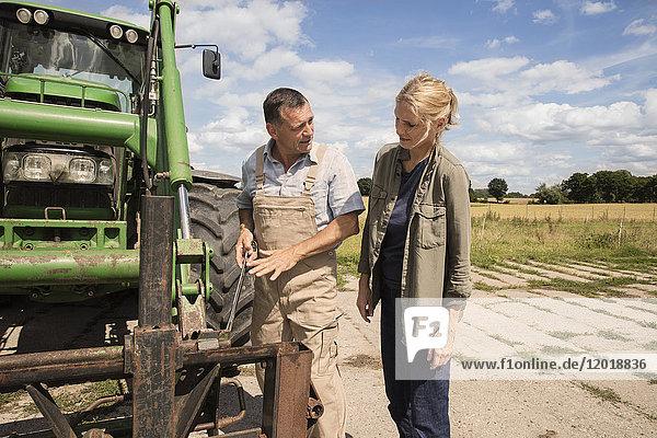 Mann  der die Frau erklärt  während er auf dem Bauernhof an einer Landmaschine steht.