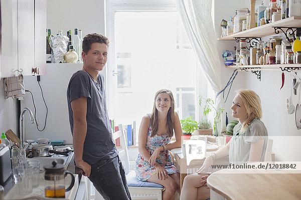 Porträt eines hübschen jungen Mannes mit Freundinnen in der Küche zu Hause