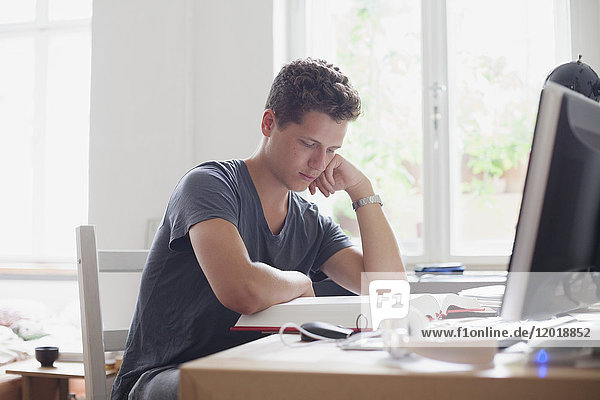 Ein junger  attraktiver Student  der zu Hause studiert.