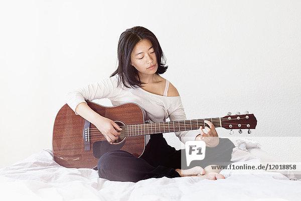 Junge Frau spielt Gitarre  während sie zu Hause auf dem Bett sitzt.