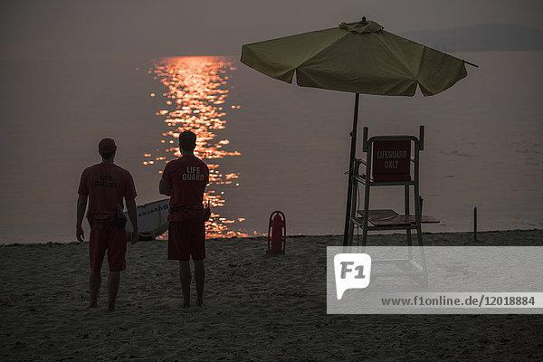Rückansicht der am Strand stehenden Rettungsschwimmer bei Sonnenuntergang Rückansicht der am Strand stehenden Rettungsschwimmer bei Sonnenuntergang