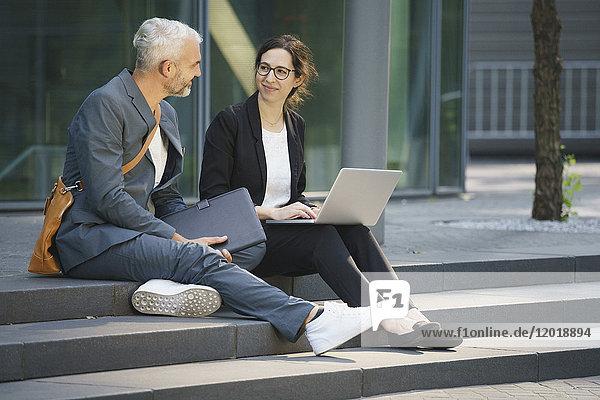 Business-Mitarbeiter mit Laptop diskutieren auf Stufen in der Stadt