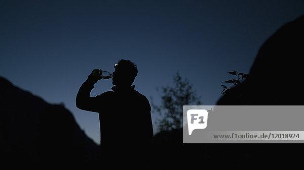 Silhouette Mann trinkt Wasser aus der Flasche  während er nachts auf dem Berg steht. Silhouette Mann trinkt Wasser aus der Flasche, während er nachts auf dem Berg steht.