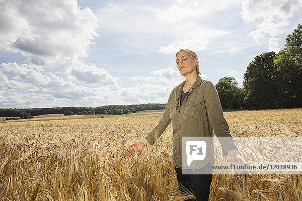 Nachdenkliche Frau steht inmitten von Weizenfeldern auf dem Bauernhof gegen den Himmel an einem sonnigen Tag.