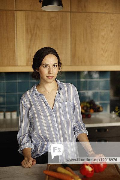 Porträt einer selbstbewussten Frau auf der Kücheninsel