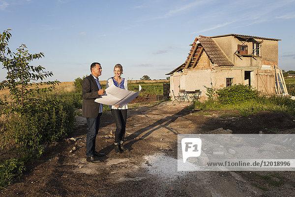 Lächelnde Frau mit Immobilienmaklerin beim Lesen des Dokuments  während sie sich gegen das Bauernhaus stellt.