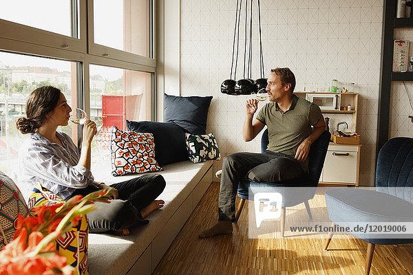 Pärchen  das Wein trinkt  während es zu Hause auf einem Fensterplatz und einem Stuhl sitzt.