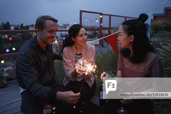 Glückliche männliche und weibliche Freunde halten Wunderkerzen auf der Terrasse.