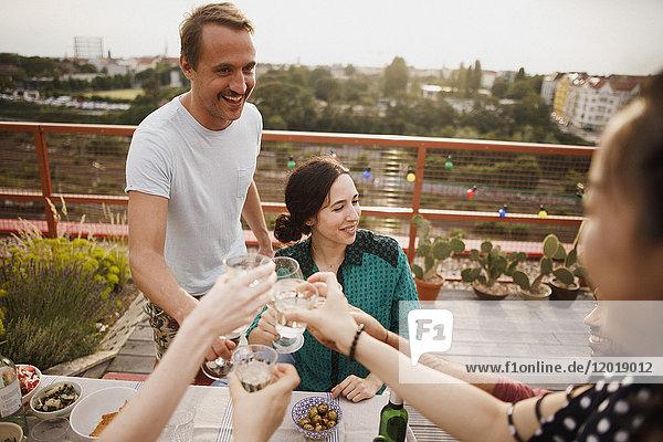 Glückliche männliche und weibliche Freunde  die auf der Terrasse anstoßen.