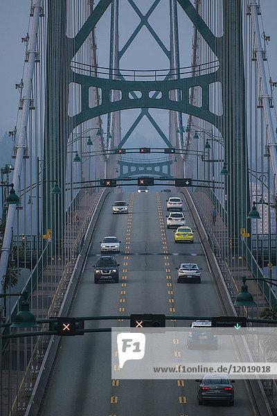 Autos bewegen sich in der Abenddämmerung auf der Brücke Autos bewegen sich in der Abenddämmerung auf der Brücke