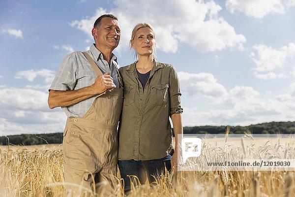 Niedriger Blickwinkel auf ein reifes Paar  das inmitten von Getreide auf dem Bauernhof gegen den Himmel steht.
