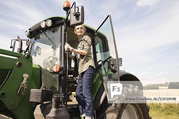 Niedriger Blickwinkel der Frau  die auf dem Traktor am Bauernhof gegen den Himmel steht  bei Sonnenschein
