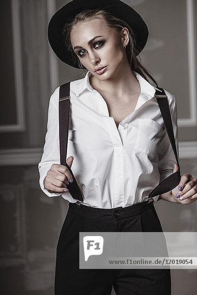 Porträt einer jungen Frau mit an der Wand stehenden Hosenträgern