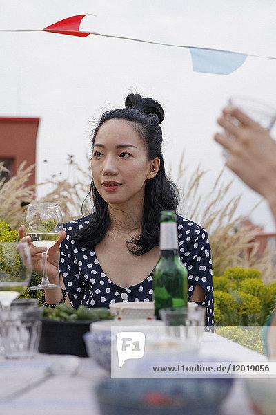 Nachdenkliche junge Frau mit Weinglas beim Sitzen am Außentisch während der Party