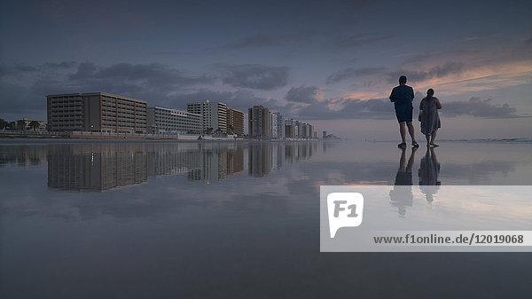 Junger Mann und junge Frau am Strand gegen den Himmel bei Sonnenuntergang  Daytona  Florida  USA Junger Mann und junge Frau am Strand gegen den Himmel bei Sonnenuntergang, Daytona, Florida, USA