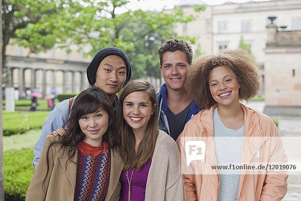 Porträt von lächelnden multiethnischen jungen Freunden im Freien