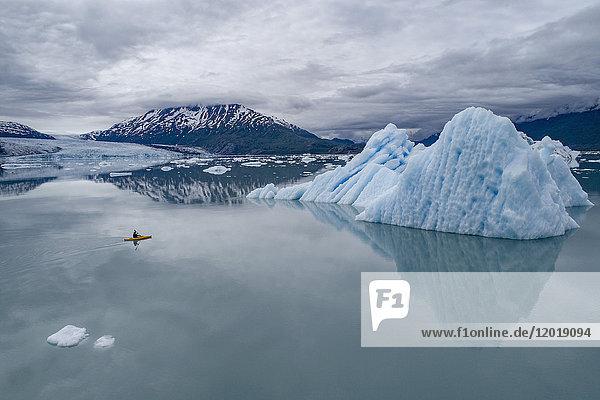 Kanufahren in der Lagune mit Eisbergen gegen bewölkten Himmel  Lake George  Palmer  Alaska  USA