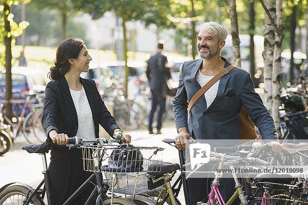 Lächelnde Kollegen im Stehen mit Fahrrädern auf dem Parkplatz