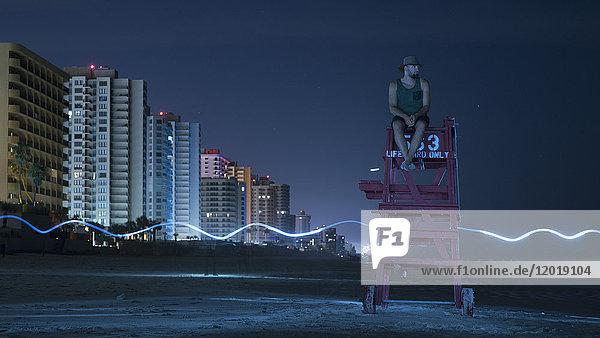 Mann auf Rettungsschwimmerstuhl gegen den Himmel bei Nacht  Daytona  Florida  USA Mann auf Rettungsschwimmerstuhl gegen den Himmel bei Nacht, Daytona, Florida, USA