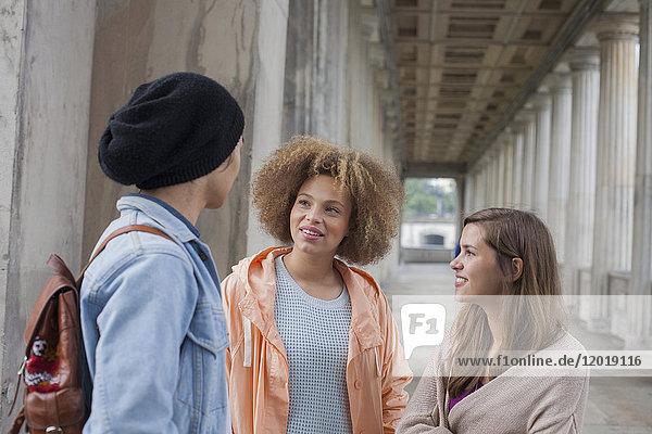Junge multiethnische Freunde beim Reden im Flur  Berlin  Deutschland