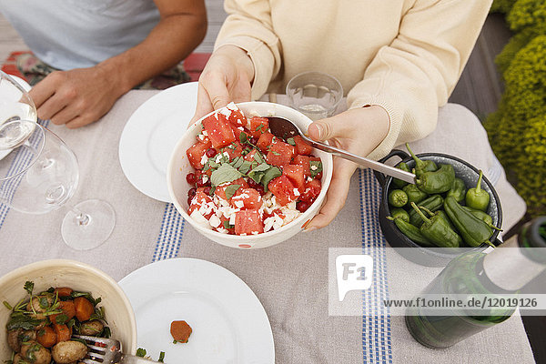 Hochwinkelansicht der Frau  die eine Obstsalatschüssel am Außentisch hält  während sie mit einem Freund sitzt.