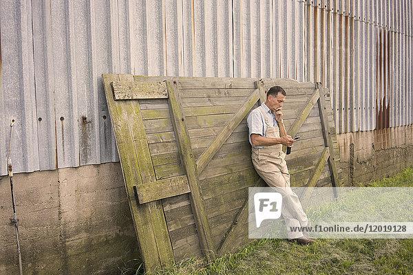 Volle Länge des Mannes  der das Handy benutzt  während er sich an die Wand lehnt.