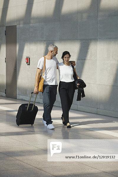 Geschäftspaar mit Rollgepäck beim Spazierengehen an der Wand am Flughafen