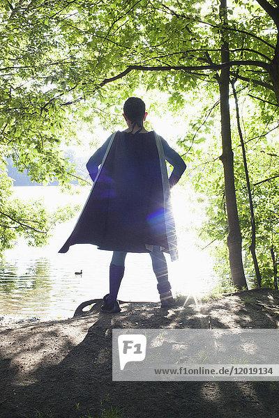 Rückansicht des Superhelden am Flussufer bei Sonnenschein