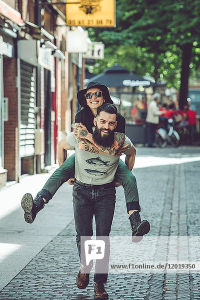 Young man carrying his girlfriend on his back in an urban environment