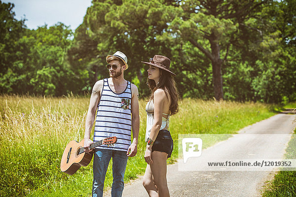 Portrait of a young couple Hipster ride in the countryside  a guitar in hand