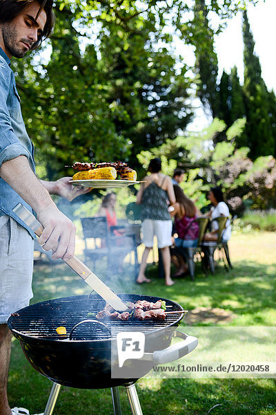 Handsome young man cooking meat in a barbecue party outdoor in the garden during summer holiday. Handsome young man cooking meat in a barbecue party outdoor in the garden during summer holiday.