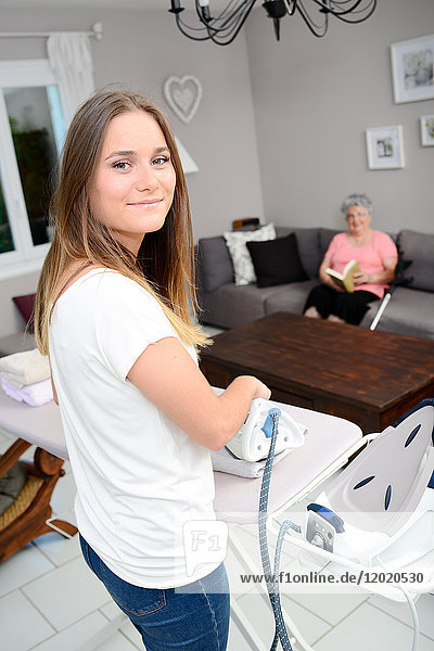 Cheerful young girl ironing and helping with household chores elderly woman at home.