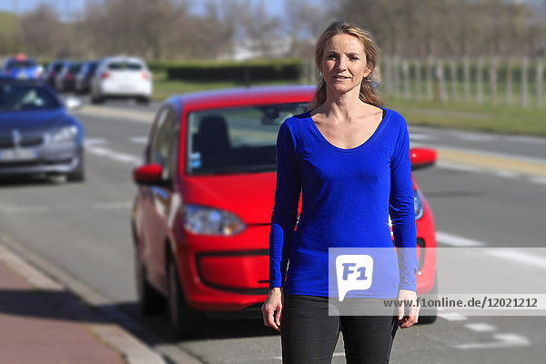 France  woman in front of her car.