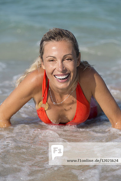 Portrait of a young smiling blonde woman lying in the sea in red swimsuit.