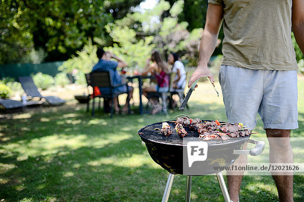 Close up of a barbecue grill with meat and sausages cooking during a summer garden party with people in background. Close up of a barbecue grill with meat and sausages cooking during a summer garden party with people in background.
