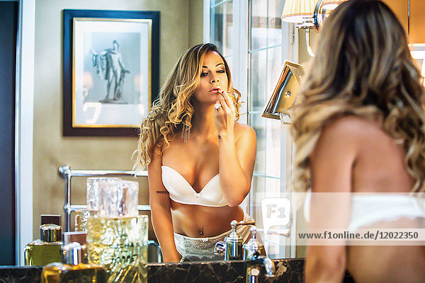 Portrait of a young face of woman in white underwear  making up in front of a mirror.