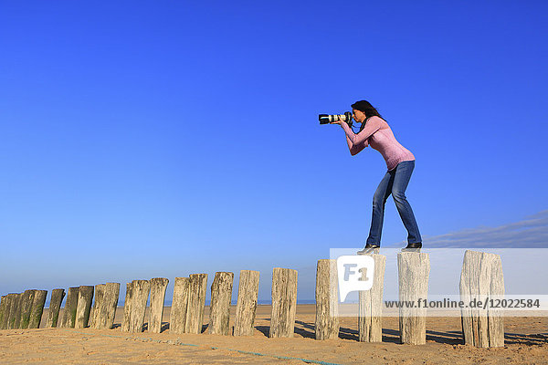 Woman at beach with professional camera