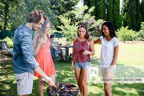 Groupe of happy and cheerful young people having fun around barbecue grill during summer holiday party outdoor in the garden.