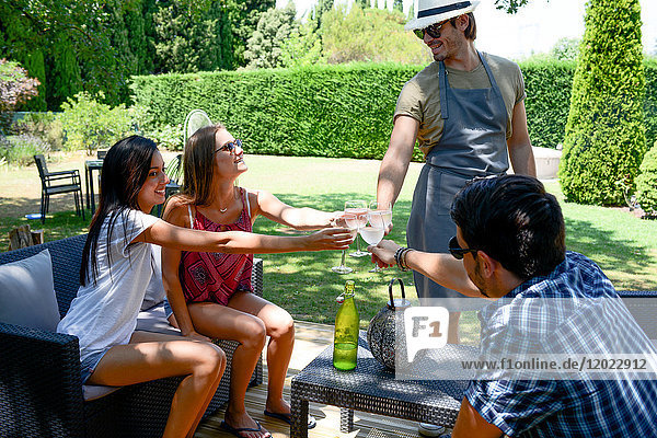 Group of young and cheerful people having a toast in a garden party outdoor in the backyard during summer holiday.