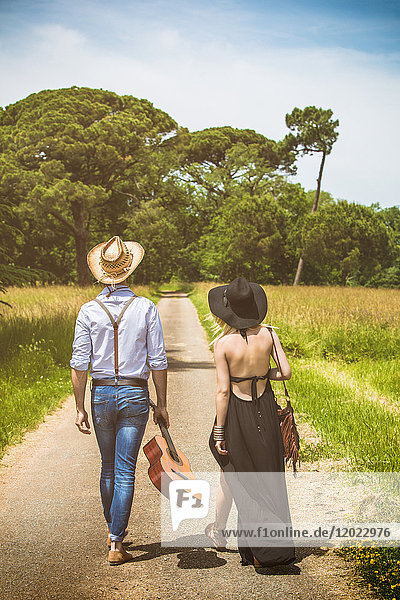 Young couple Hipster ride in the countryside  a guitar in hand