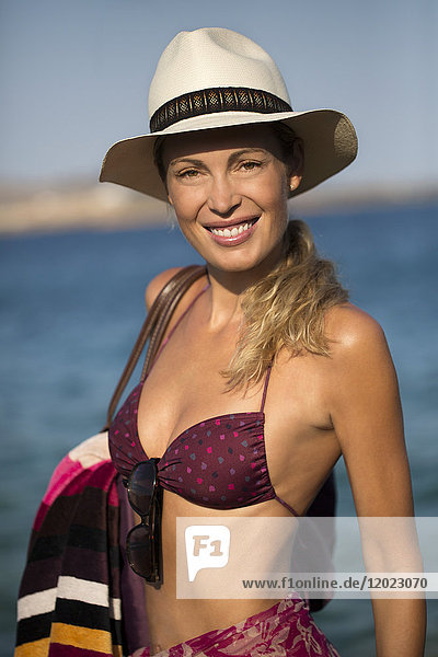 Portrait of a smiling young blonde woman in a swimsuit   sun hat and beach staff going to the beach .