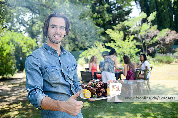 Handsome young man showing grilled meat in barbecue party outdoor in the garden during summer holiday. Handsome young man showing grilled meat in barbecue party outdoor in the garden during summer holiday.