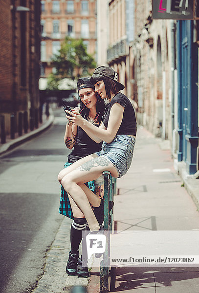 two young women captivated by a mobile phone in an urban landscape