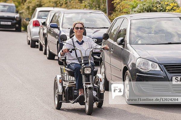 A woman on her shopping trike in Walberswick   Suffolk   England   Britain   Uk.