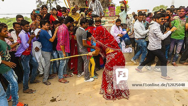 Women with lathis (sticks ) chasing and beating men  Chhadi Mar Holi  local Holi celebration (festival of colors)  in the village of Gokul  near Mathura  Uttar Pradesh  India.