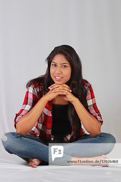 Young Indian girl in casual attire sitting cross legged.