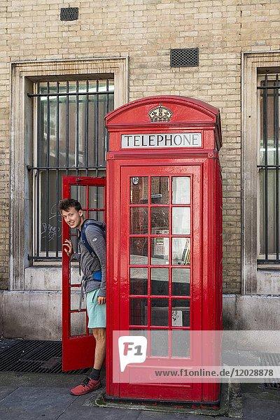 Junger Mann kommt aus rote Telefonzelle heraus  London  England  Großbritannien  Europa Junger Mann kommt aus rote Telefonzelle heraus, London, England, Großbritannien, Europa