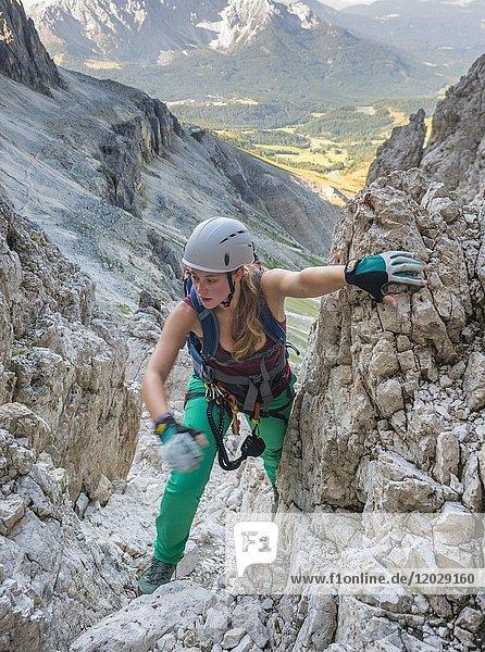 Hiker climbs the Santner via ferrata  view of Latemar Group  Rosengarten Group  Dolomites  South Tyrol  Trentino-Alto Adige  Italy  Europe