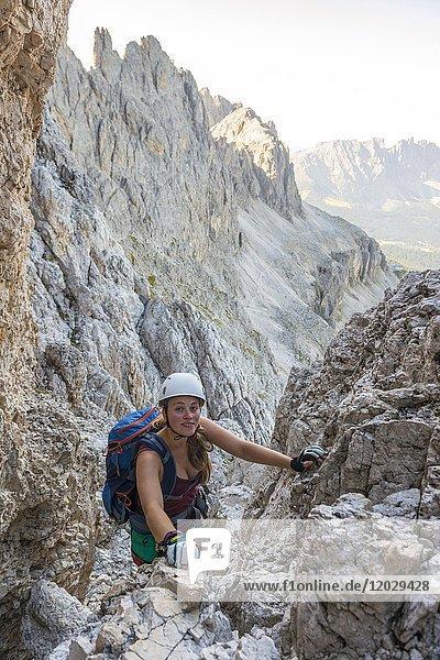 Wanderin klettert am Santner-Klettersteig  Rosengarten-Gruppe  Dolomiten  Südtirol  Trentino-Alto Adige  Italien  Europa